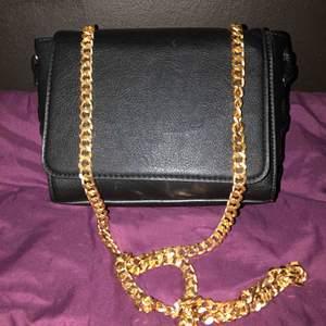 Ny fin svart axel väska med gulddetalj och kedja axelband väldigt fin.  Finns i Västerås att hämta eller postas och köparen står för frakten.