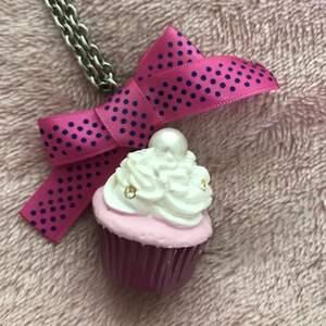 Ett långt halsband med en stor rosa cupcake på 😍 Cupcaken är ca 5-6 cm hög och har en rosa rosett kring sig 💕💗 Supersöt, fint skick, väldigt Lolita ✨