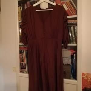 Brun klänning från Ellos i strl 44. Använd 1-2 ggr. Frakten betalas av dig som köper.