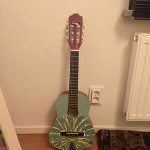 En liten gitarr som är målad, färgen går säker att ta bort om man vill! Den fungerar bra och är stämd.