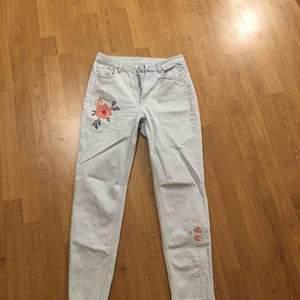 En jeans med 2 blommor fastsytt på