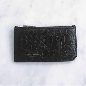 YSL / Saint Laurent plånbok/korthållare. Använd, i ok/bra skick. 5 fickor för kort och ett fack med dragkedja för mynt/sedlar. Mycket bra kvalite, använd men i bra skick. I mitt pris så bjuder jag på frakten! :)