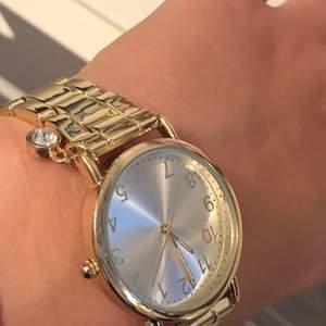 En guld klocka med en fin liten diamant detalj som är helt oanvänd. Köpte för väldigt länge sedan så vet inte vart jag köpte den. Det ligger även en extra del i lådan så att man har möjligheten att göra klockan större.
