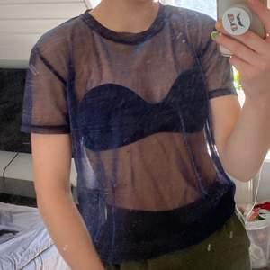 En genomskinlig t-shirt gjord av trådar som skiftar färg mellan rosa och blå. I vissa ljus skimrar det rosa och i andra blå. Snygg passform med något loose-fit även fast den är XS. Perfekt som festlig outfit.