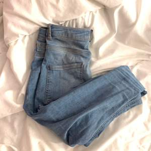 ljus blåa jeans med egna hål. highwaist och bra passform över rumpan.