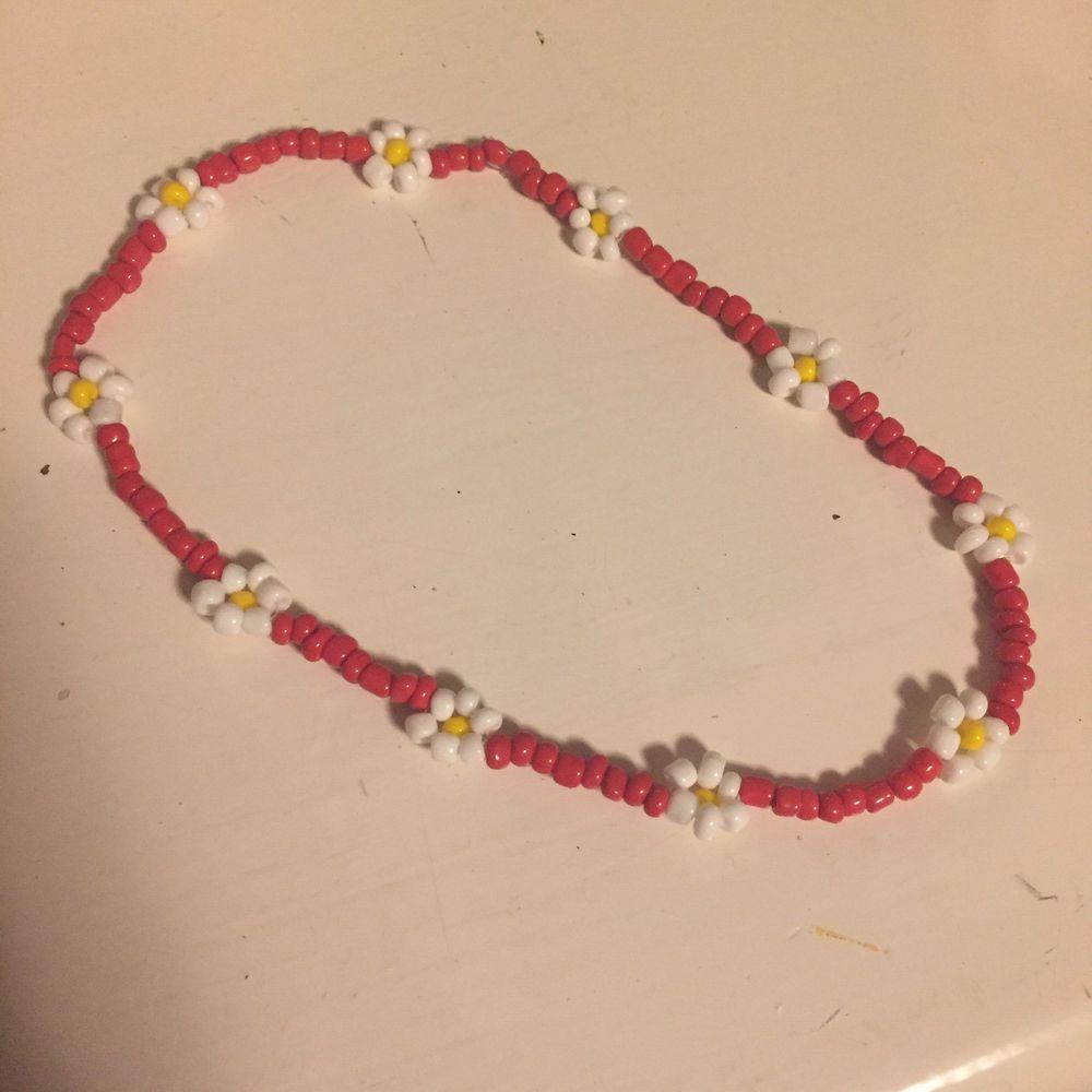 Fint rött halsband med vita blommor🌸🦋. Accessoarer.