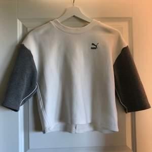 En sweatshirt med tre-kvarts ärm från Puma. Vitt plagg med grå ärmar och tryck. Är i storlek: 11-12 år men klassas som XS. Använd fåtal gånger. Köparen står för eventuell fraktkostnad.