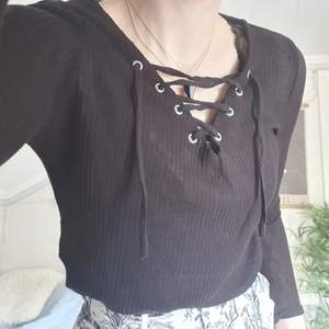 basic svart tröja med snörning över bröstet.