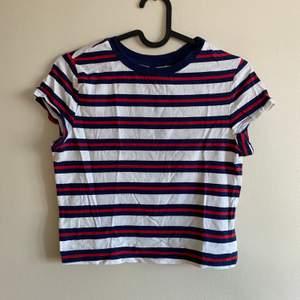 Croppad T-shirt i stretchiga material. Passformen är figurnära. Ränderna är blåa och röda.