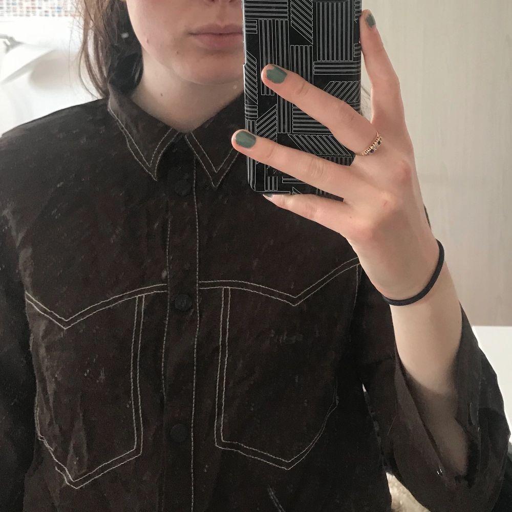 skjorta från zara brun med vita sömmar! jättecool! Storleken är Large men har krympt så mer Small/XS. Skjortor.