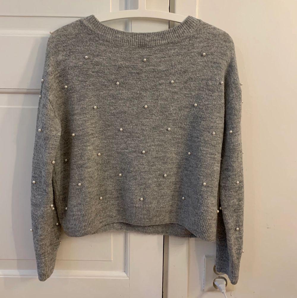 En grå stickad tröja med väldigt fina detaljer i form av pärlor, tröjan kommer tyvärr inte till användning längre . Stickat.