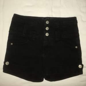 Svarta högmidjade shorts.