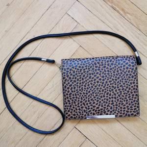 Liten axelremsväska som får plats med allt man behöver för en utekväll. Leopard mönstrad svart/brun. 5 fack/fickor. Tryckknapp.
