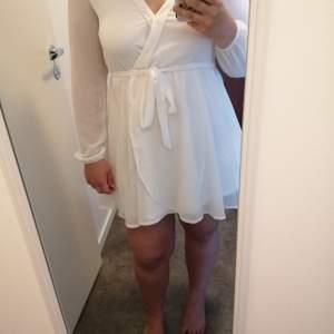 Fin, vit klänning i omlotteffekt i fint skick. Använd högst 2-3 gånger.