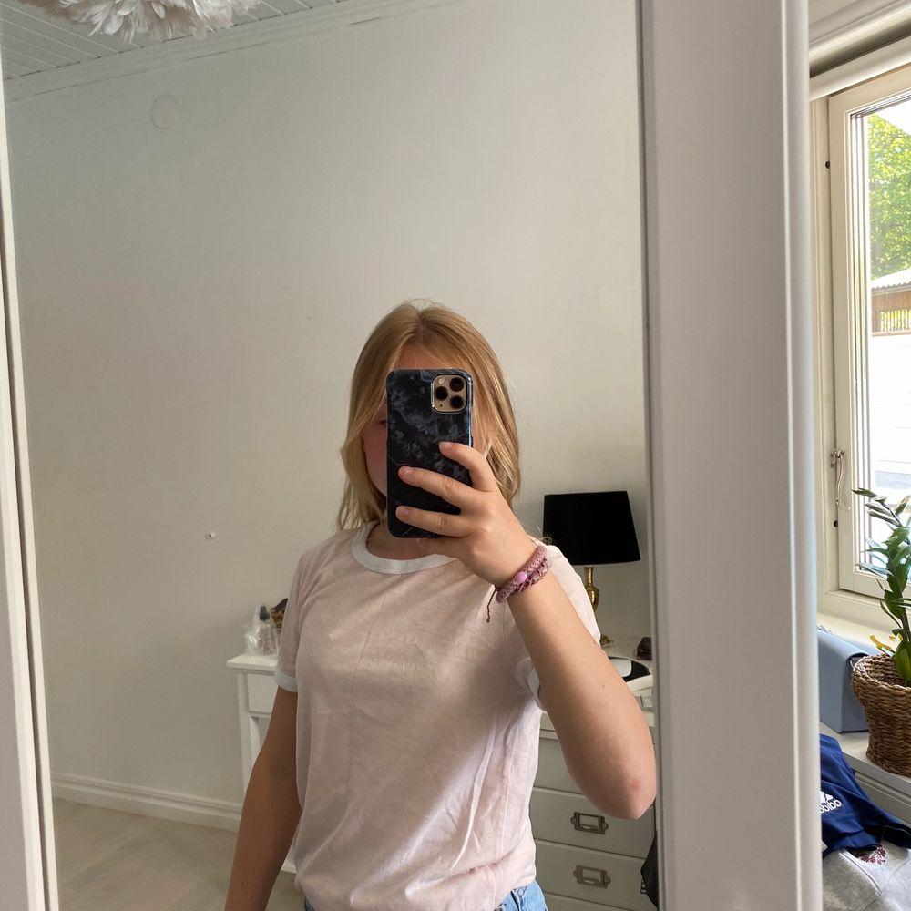 En rosa tröja med vita detaljer runt armarna och kragen, den kommer från H&M och nypris var 125kr. Buda från 50 kr. T-shirts.