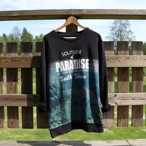 Svart sweatshirt med paradis tryck. Använd men fortfarande i fint skick. Storlek XL. Frakt är inkluderat i priset.