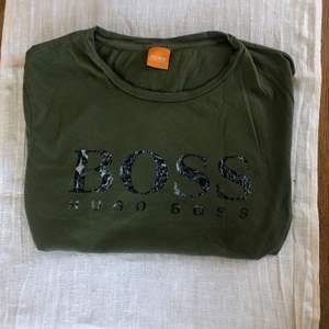 Grön t-shirt från Hugo Boss som knappast är använd, det är storlek M men den är relativt liten i storleken. Pris exkl frakt :)