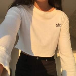 Säljer denna vita cropped tröja från Adidas🤍⚡️ Äkta! Otroligt bekväm med dens tunna tyg som sitter skönt på! Fint att använda den som den är, eller med en spetstopp under💞  Fint skick! Passar en S! Kontakta gärna vid intresse🥰