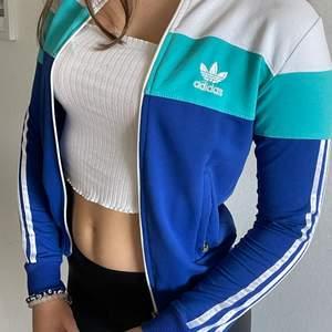 Jätte snygg adidas zip tröja med blå och vita detaljer. Knappt använd men kan vara sjukt snygg till många outfits, och är lite i 2000-tals stil. Såå snygg!😍😍