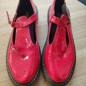 Ett par chunky sandaler i Mary Jane-stil med gul kontrastsöm i gummisulan. Iögonfallande rött lackigt material som glänser i solen. Finns även spänne fram för att reglera storleken. Aldrig använda då de ej passar mig, men har fått lite märken av förvaring, se bilder.  Innermått 26,5cm, vilket motsvarar ca storlek 40,5/41.   Avhämtning i Vällingby, Stockholm eller skickas mot frakt.