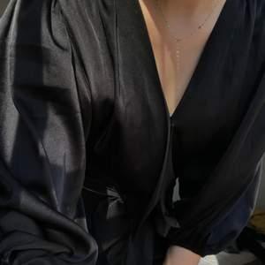 Snygg svart blus som kan användas till alla tillfällen- allt från skola till fest! Det är en vringad magtröja som knyts framför magen