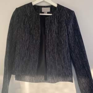Svart Kavaj med silver inslag, super festlig och så snygg att matcha med svarta kostym byxor t.ex. kort i modellen. Toppskick