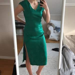 en otroligt vacker klänning i skimrande magisk grön färg, superelegant och oanvänd då den tyvärr är för stor 😭 håller in midjan på mig av den anledningen för att visa hur den ska sitta, skulle rekommendera till en 38/40. slitsar i benen och dragkedja i sidan. perfekt till fest, skolavslutning eller bal! skriv så kommer vi överens om ett pris.