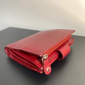 En Don Donna plånbok som jag haft i cirka ett år. En smidig liten plånbok i skinn med många praktiska fack. Lock med spänne och knapp framtill samt fack med dragkedja baktill.