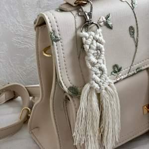 Handgjord Makramé nyckelring i färgen vit . Låset har en 360 graders rotering. Supersnygg att fästa i sina nycklar eller tex. på sin handväska. Den är oanvänd! Finns även med kortare fransar. 50 kr styck & frakt på 12 kr tillkommer!