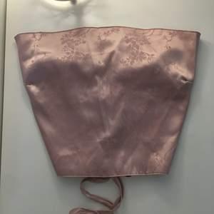 Jättesöt ljusrosa (lite åt det lilla hållet) topp i satin material med blommigt mönster. Aldrig använd, går att skjutsera som önskas med banden i ryggen. Storlek M.