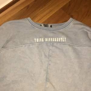 En blå tränings tröja på fram och baksida