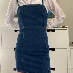 Mellanblå kort jeansklänning från Pull and Bear, stl S. Skönt, elastiskt material som formar sig efter kroppen: 98% bomull, 2% elastan. Perfekt till sommaren!