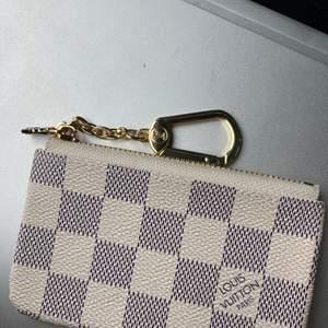 Louis Vuitton plånbok/korthållare. Du kan ha ditt kort, nycklar, kontanter där i osv. Kan inte garantera äktenhet där av priset
