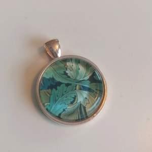 Halssmycke i silverfärgad metall och glas. Med motiv av William Morris. Nickelfritt. 25 mm i diameter. Budgivning!