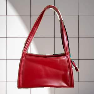 Megasnygg handväska i vinröd färg. Mycket rymlig, stängs med dragkedja. Liten märkning på ena sidan, se sista bilden. Väskan har en innerficka med dragkedja. Väskan har lite klister från en gammal prislapp, men går antagligen att ta bort. Fri frakt.