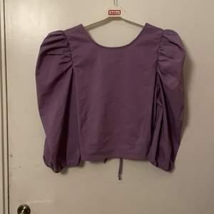 Pastel lila tröja med puff armar och öppen rygg med stören. Väldigt ny och knappt använd