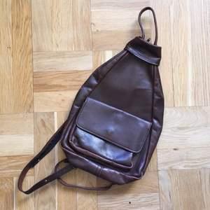Vintage ryggsäck med varierbara remmar som gör att man kan ha den snett mer som en magväska, eller som en ryggsäck när man delar på dragkedjan. Tjockt, mjukt läder i följsam kvalitet. Storlek 23x7x33 cm.