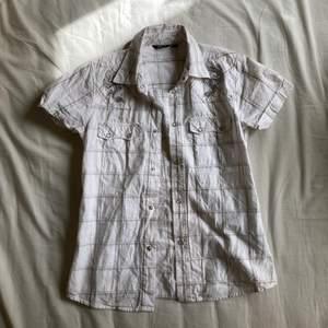 Vit tajt skjorta med en silver drake på ärmarna. Det sitter väldigt fint, frakt:24