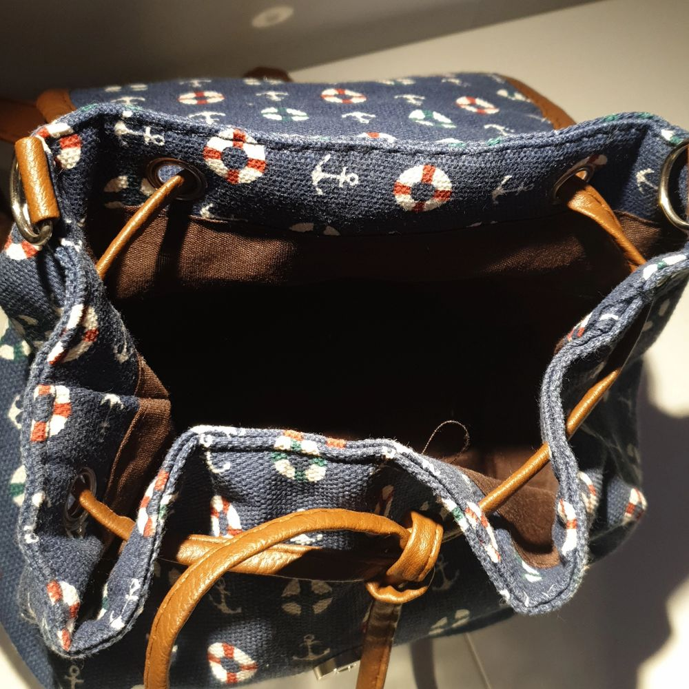 En liten ryggsäck med havsrelaterat mönster. Rymmer ganska mycket för att vara en sådant liten ryggsäck. Har en liten ficka med dragkedja och är i ett bra tillstånd.. Väskor.