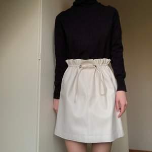 Paperbag stil. En vit kjol i läderimitation från Gina Tricot; orginal pris 399 kr. Storlek 34 men kan passa 36-38 tack vare spännbanden. Endast buren en gång, perfekt skick. Frakt: 79 kr eller mötas i Malmö.
