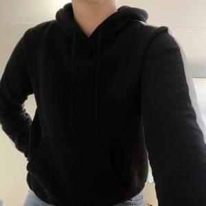 En svart hoodie med vita ränder på ärmarna. Passar storlek S-M. Väldigt bra skick.