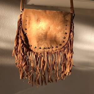 """Brun väska i bohoo stil med fransar. Stängs med magnet och har en liten ficka. Har ändringsbart axelband med """"smuts guldiga"""" spännen."""