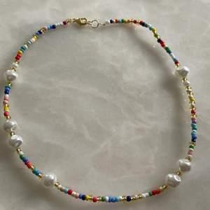 Handgjort halsband i olika fina färger med olika större vita pärlor till. Halsbandet är EJ elastiskt men det tillkommer spänne och man kan även önska en viss storlek. Finns endast ett av detta därför är det först till kvarn!!