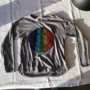 Grå långärmad tröja med paljetter av form av en smiley. Fint skick! Checka gärna in mina andra försäljningar☺️ Frågor? Bilder? Skicka så fixar jag det!