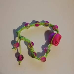 Fräsigt armband med en rosa dödskalle på. Kolla in bion för mer info
