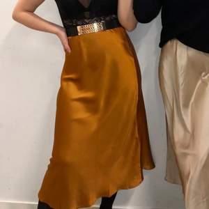 Midi-kjol i glansigt material. Resår i midjan. Använd en gång. Fler bilder kan tas vid önskemål. Frakt tillkommer.