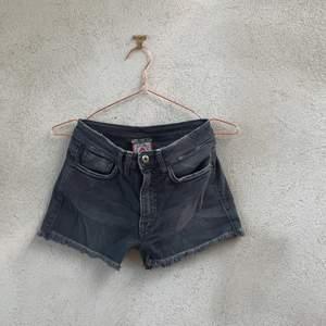 Svarta fransade shorts, med nitar vid fickorna samt märke på högra bakfickan.