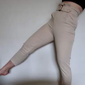 Snygga byxor i beige som funkar till både fest och vardag. Löstagbart bälte medföljer. Nyskick.