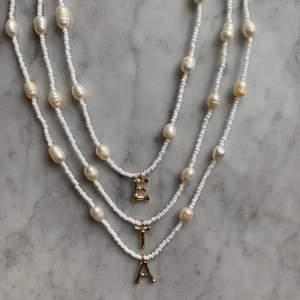 Halsband som är handgjorda, bra hållbarhet! Gjort på glaspärlor & äkta sötvattenspälor🤍 kolla in @emmaxjewelry på Instagram 🤍 finns alla bokstäver förutom Ä, Å, Ö, finns även i silver