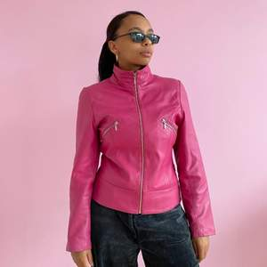 Leather jacket in pink/fuchsia with two breast pockets. In good condition